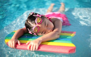 a little girl rests in a pool on a rainbow-colored swimming board